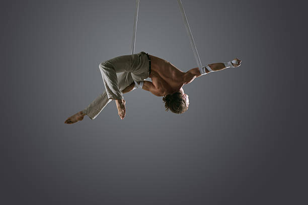 Man performing aerial silk straps stock photo