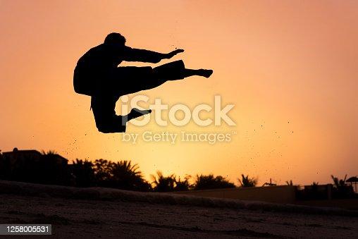 Man performing flying karate leg jump kick at the beach at sunset silhouette