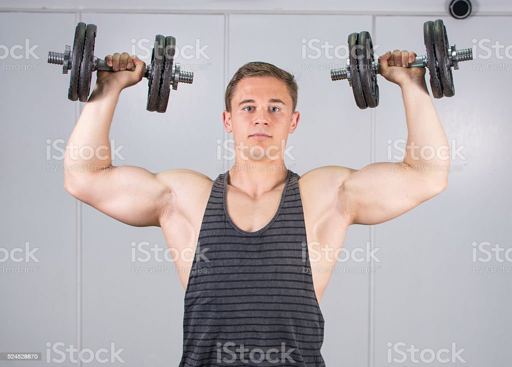 Man performing shoulder workout at the gym stock photo