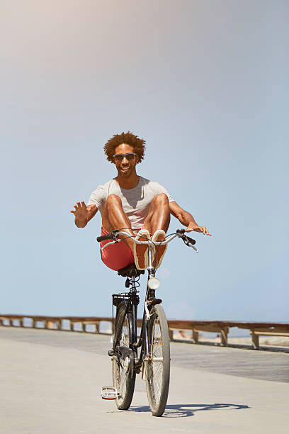 Man performing stunt on bicycle against blue sky - Photo