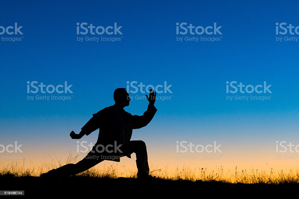 Man performs Tai Chi sport at dusk stock photo