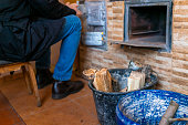 Man person sitting on chair in rustic dacha country home or house cottage living room by fireplace by buckets with wood logs for cooking