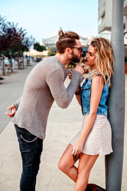 Man persuading a girl to kiss Man persuading a girl to kiss while she is pulling his sweater man bun stock pictures, royalty-free photos & images