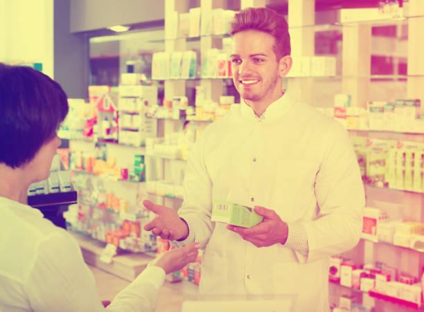 mann apotheker helfen kunden in drogerie - spanische rezepte stock-fotos und bilder