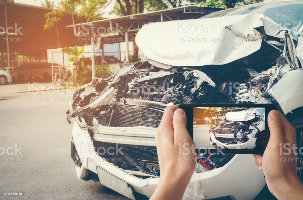 A man photographed his vehicle with accidental damage with a smart phone.Car Insurance Concept stock photo