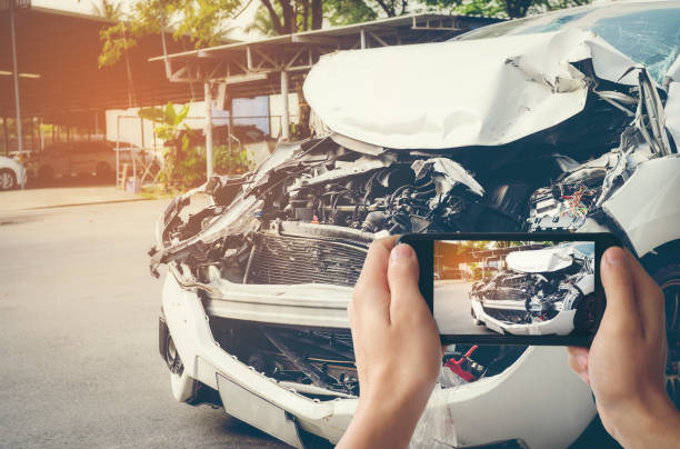 a man photographed his vehicle with accidental damage with a smart phone.car insurance concept - car accident stock photos and pictures