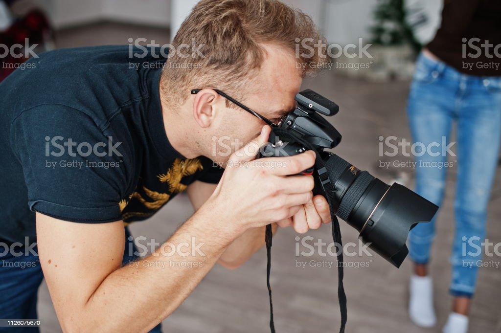 Man photographer shooting on studio. Professional photographer on...