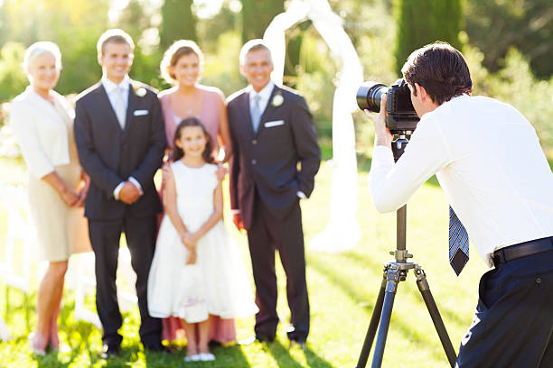 Man Photographing Family At Outdoor Wedding stock photo