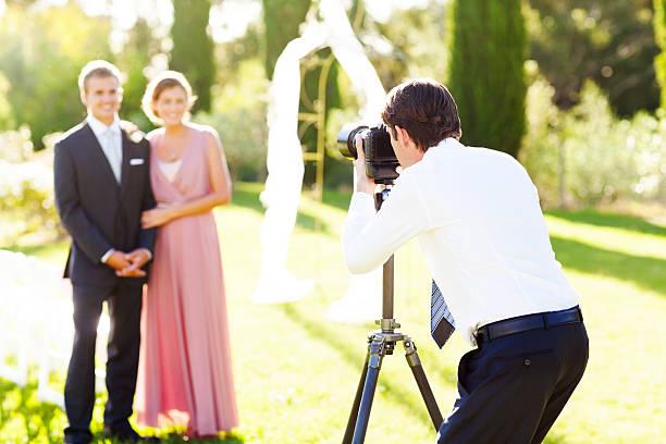 Man photographing groomsman and bridesmaid at garden wedding picture id181061286?b=1&k=6&m=181061286&s=612x612&w=0&h=fpwra8n qq l2ndeamwvzyfqxvyjcbuvd 2cbfapo0k=