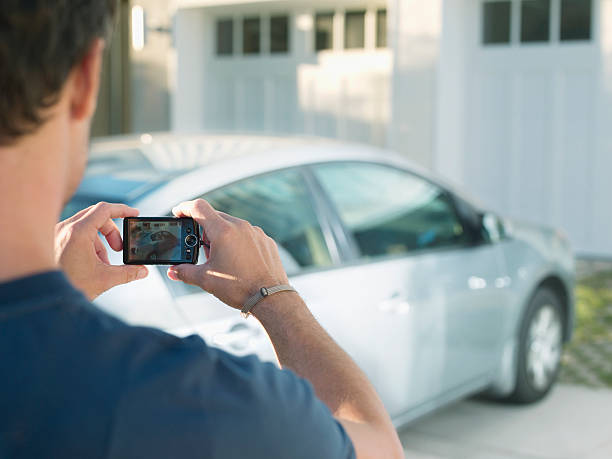 Man photographing new car stock photo