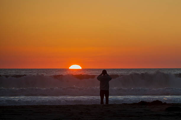Man photographing sunset over the ocean stock photo