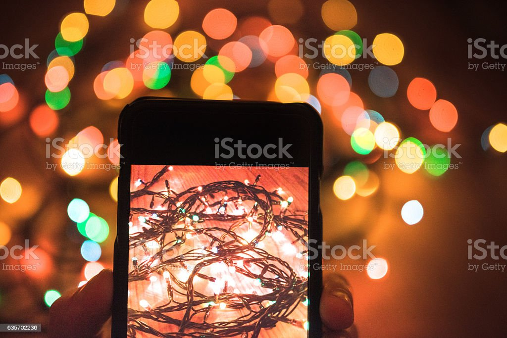 man photographing the christmas lights with the smartphone royalty-free stock photo