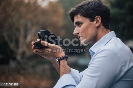 Handsome, young man standing in park and taking photos with instant camera.