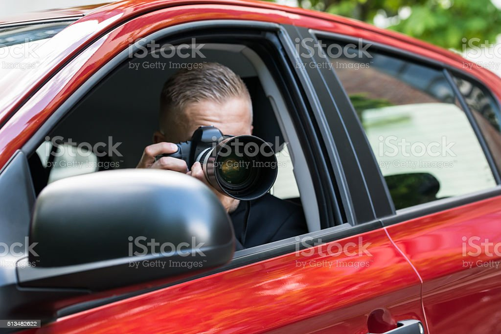 Man Photographing With Slr Camera From Car stock photo