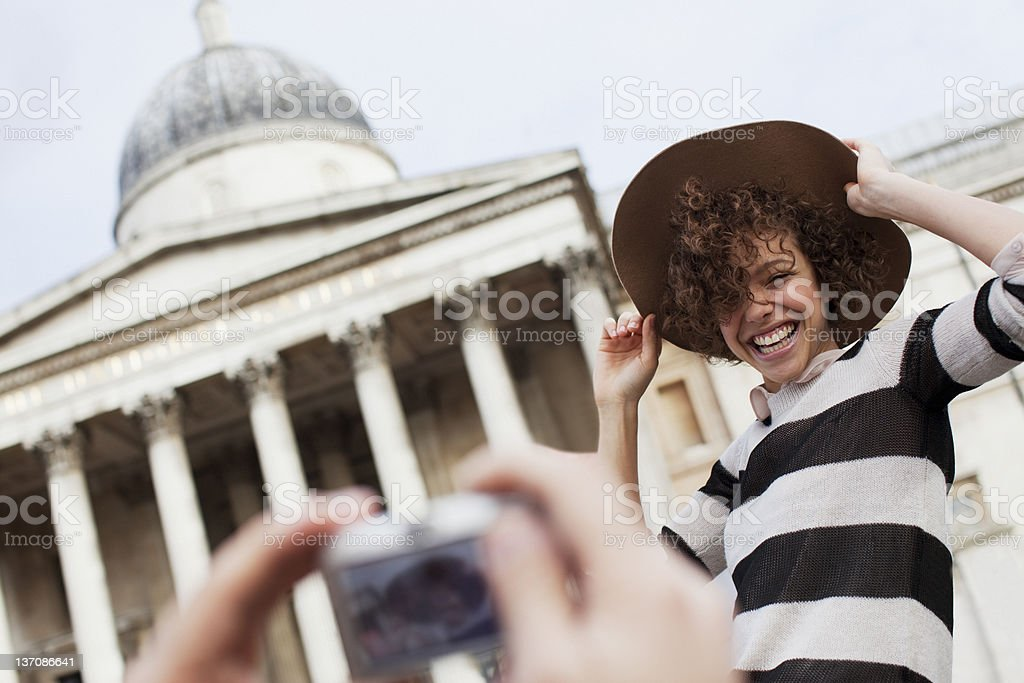 Man photographing woman with hat in front of historical landmark stock photo