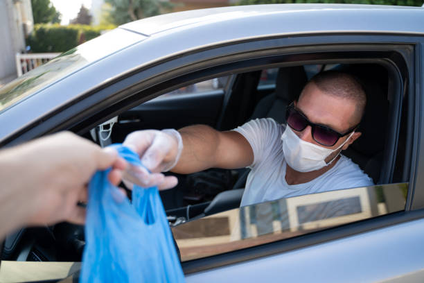 Man picking his restaurant food or package from his car at a pick up curve. during pandemic man picking up the food, pizza he ordered to the car. during pandemic coronavirus covid 19 curbsidepickup stock pictures, royalty-free photos & images