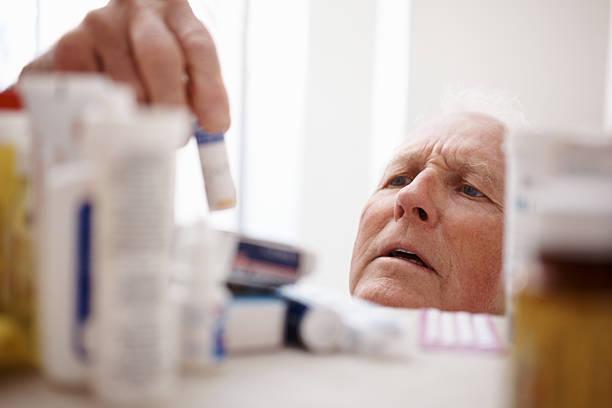mann abholen medizin-flasche von einem regal - lieblingsrezepte stock-fotos und bilder