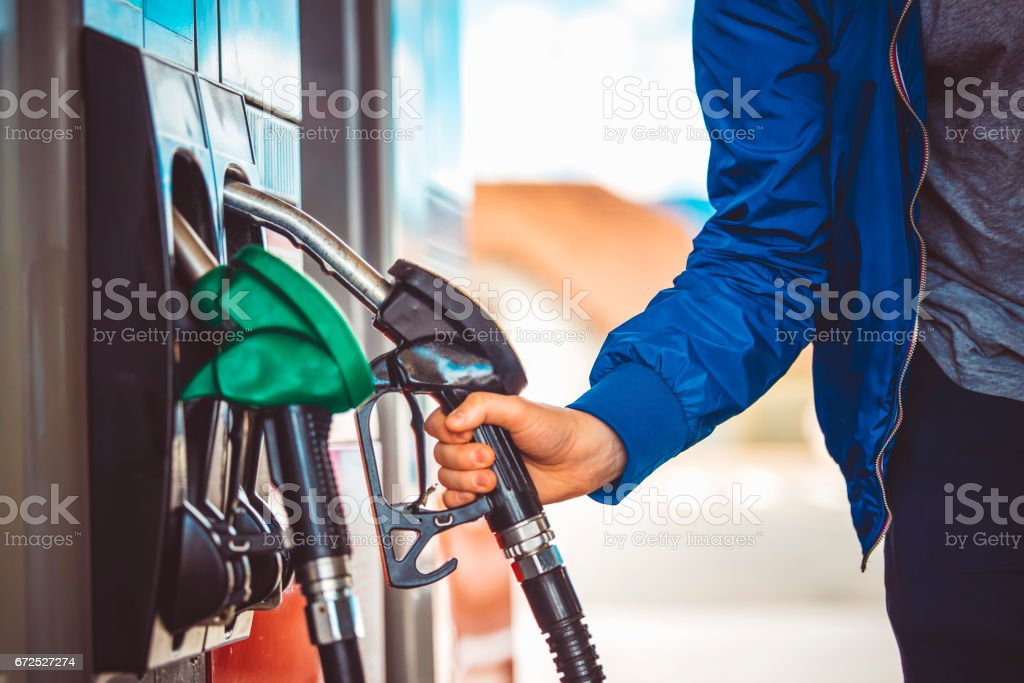 Man picking up fuel nozzle stock photo