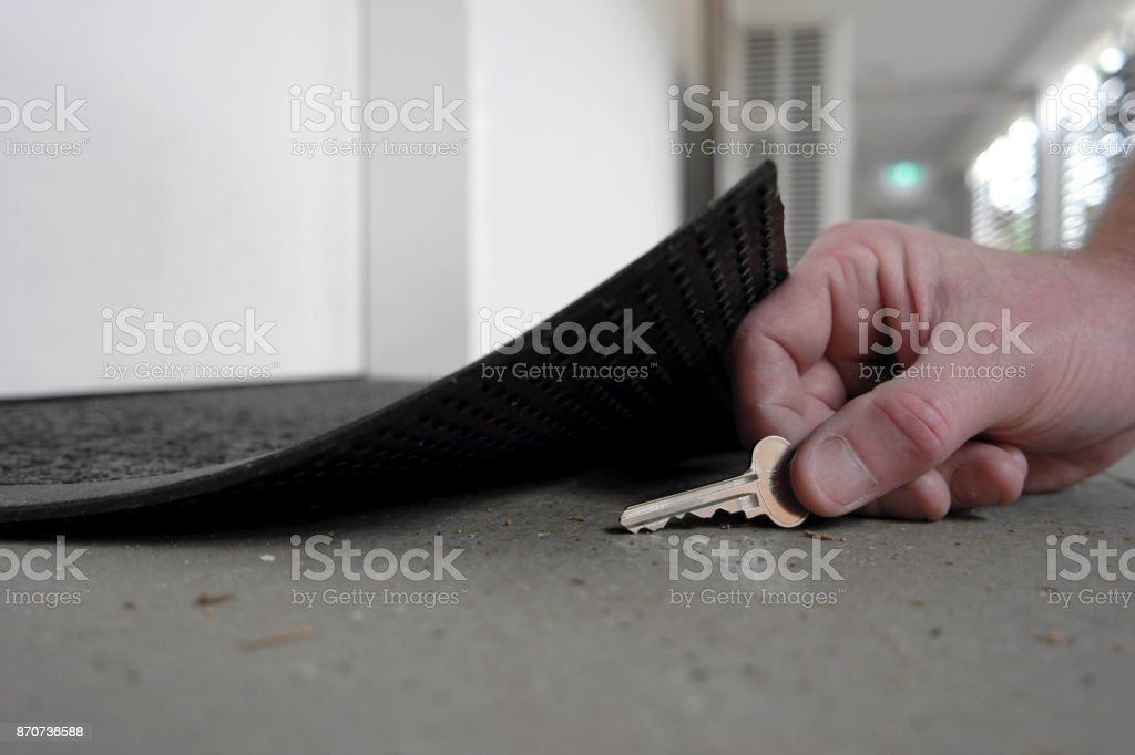 Man picking up or hiding a key under the door mat stock photo