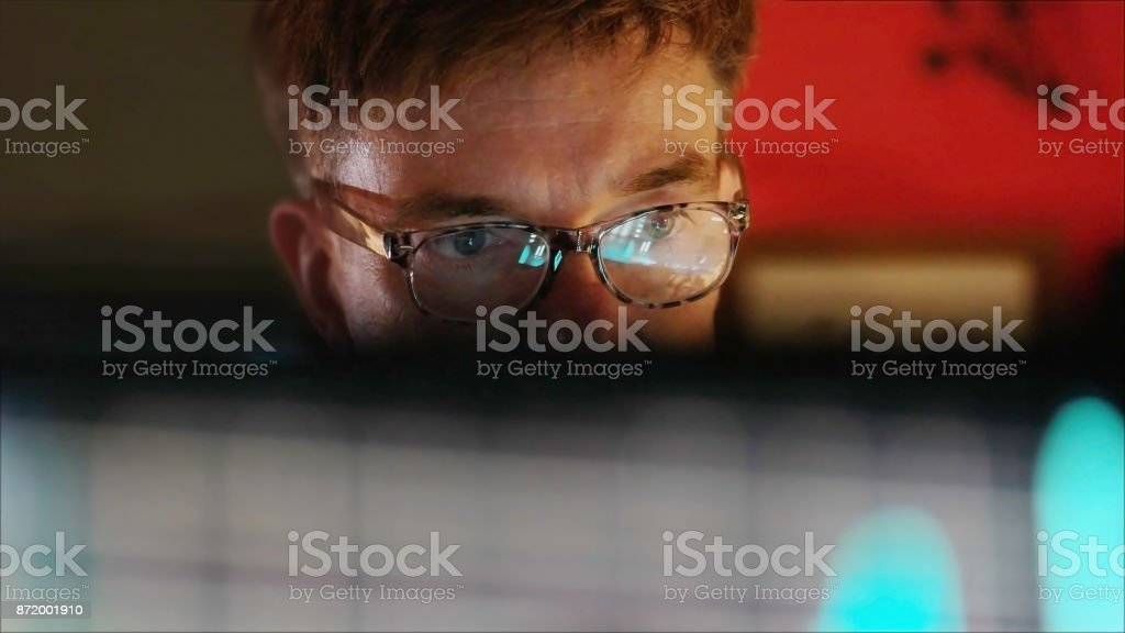 IT man A mature man studying a colourful computer display which is reflected in his glasses. Lines of computer code are visible in the reflection as he intently watches the screen. He is surrounded by out of focus monitors displaying moving, colourful, data. Adult Stock Photo