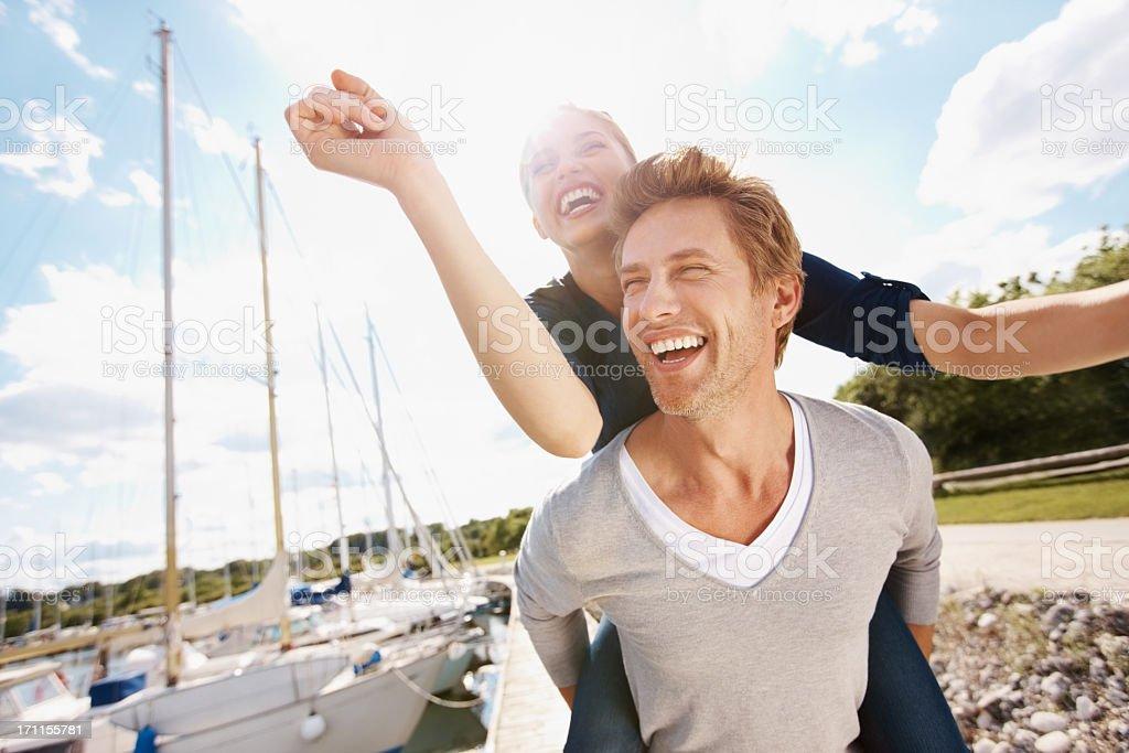 A man piggy backing a woman having a lot of fun royalty-free stock photo