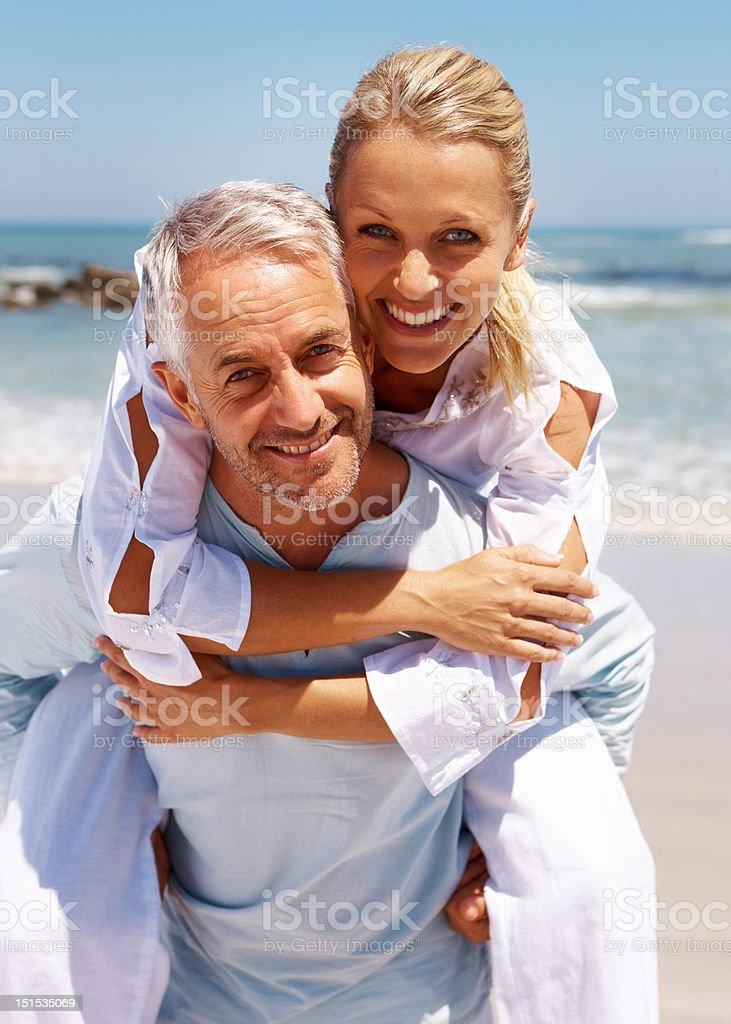 Man piggybacking his wife at beach stock photo