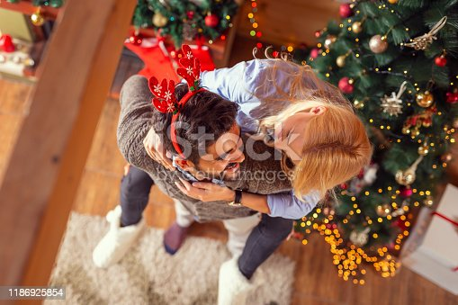 istock Man piggybacking his wife next to a Christmas tree 1186925854