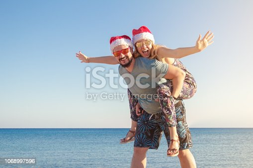 man piggybacking to his girlfriend in christmas hats and sunglasses at the beach of the sea.