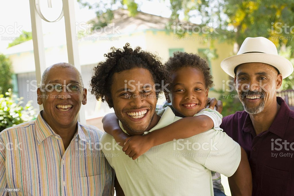 Man piggybacking young boy with two older men standing beside him stock photo