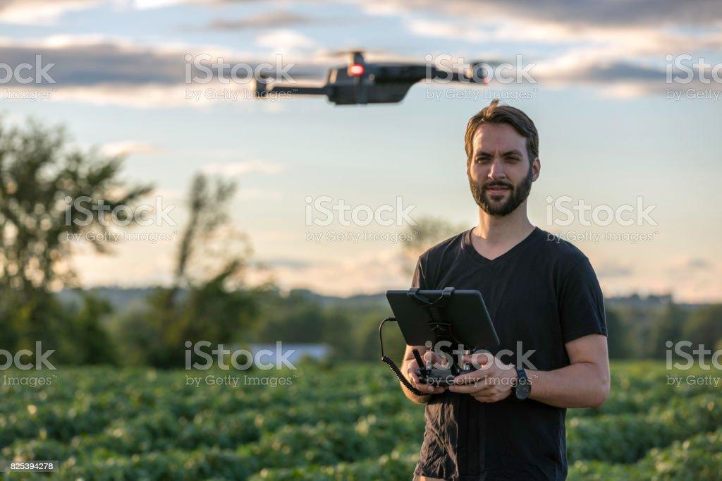 Piloto de hombre con mando a distancia robot al atardecer - foto de stock