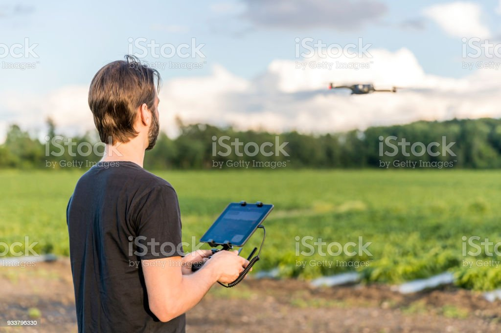 Man Pilot Using Drone Remote Controller at Sunset stock photo