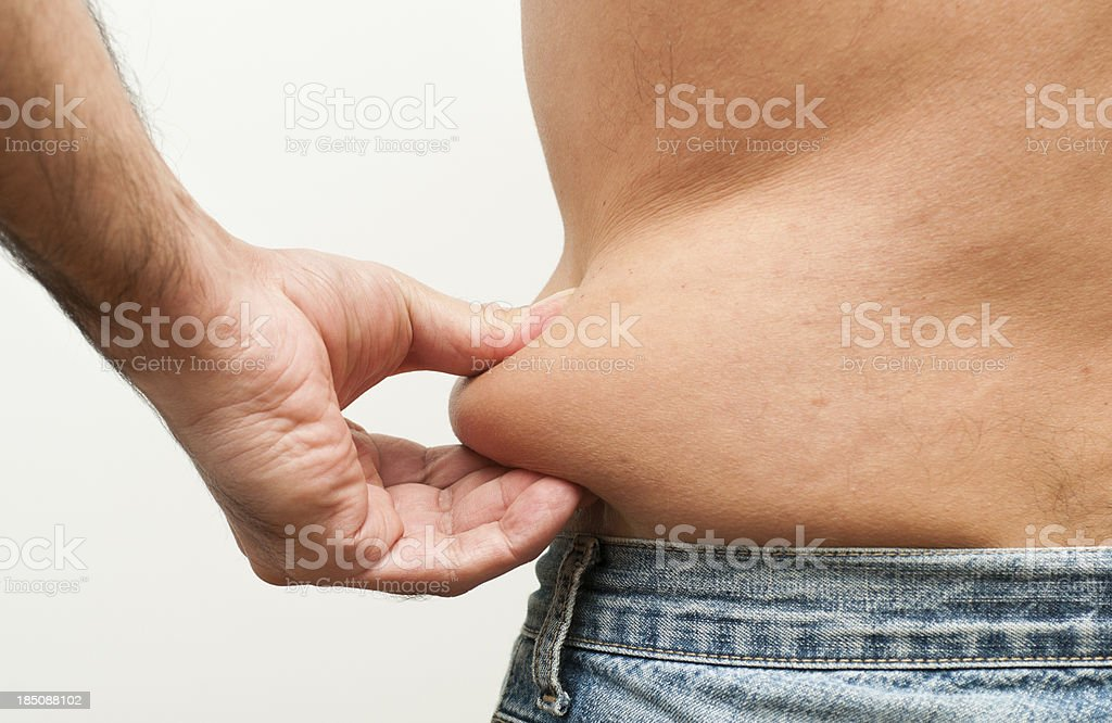 A man pinches his fat from his belly area stock photo