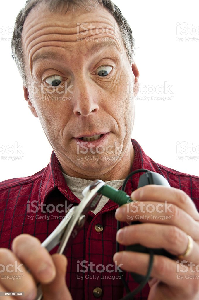 Man pinching a PS2 plug with pliers royalty-free stock photo