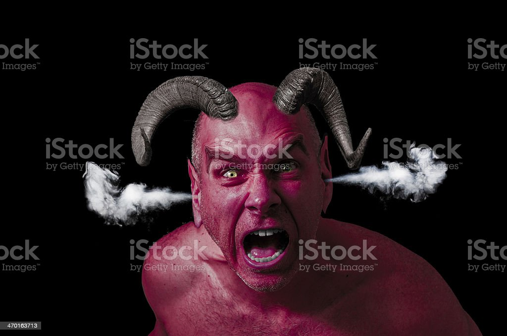 Man pissed off with red skin and horns stock photo