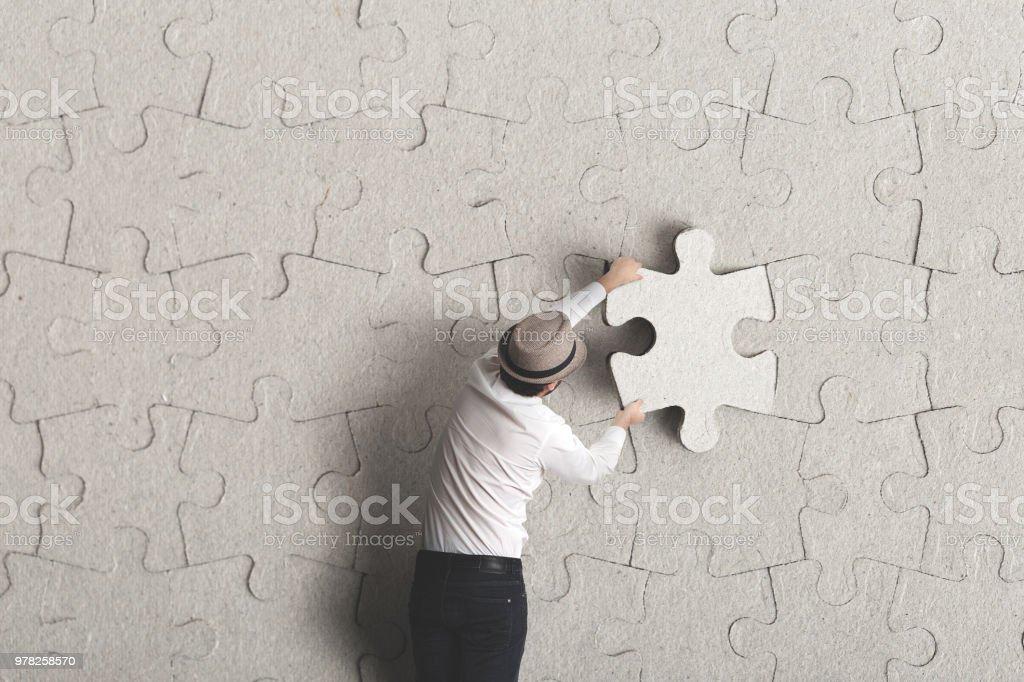 man places last piece of puzzle surreal concept stock photo