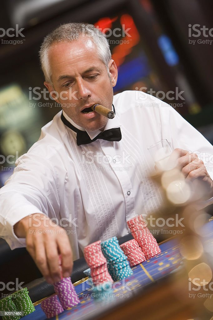 Man placing bet at roulette table royalty-free stock photo