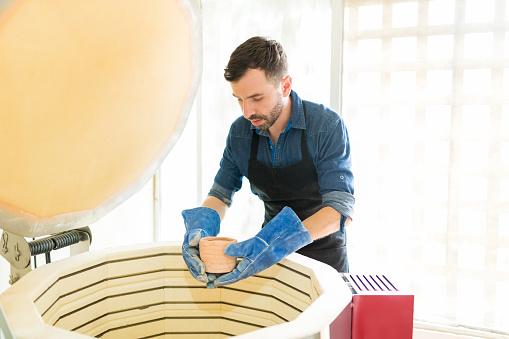 Man Placing Clay Mug Into Kiln At Pottery Studio