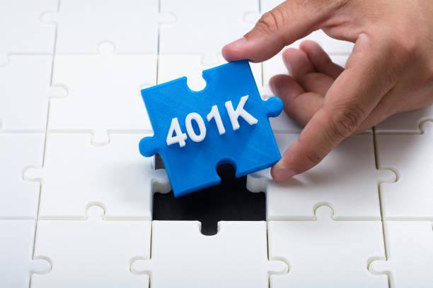 Man placing final 401k piece into jigsaw puzzle Close-up of a man's hand placing final blue 401k piece into jigsaw puzzle 401k stock pictures, royalty-free photos & images