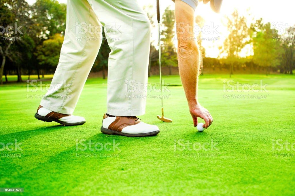 Man placing golf ball stock photo