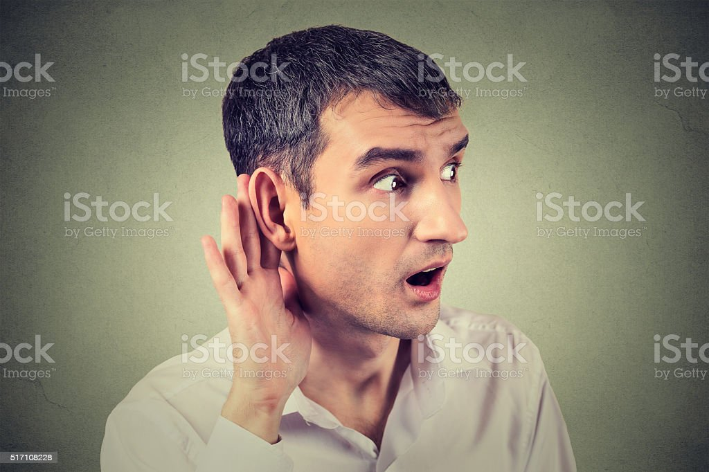 man placing hand on ear asking someone to speak up stock photo