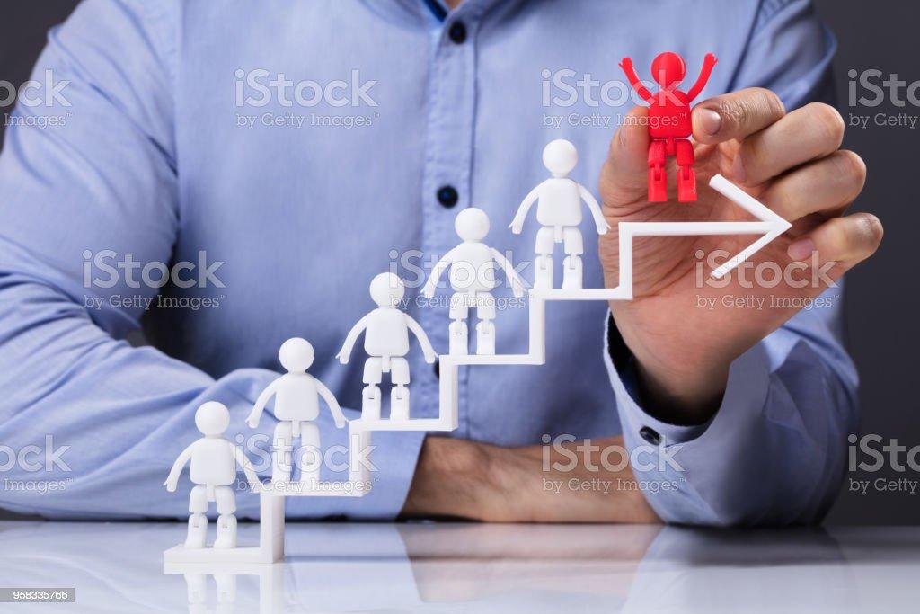 Man Placing Human Figure On Top Of White Arrow stock photo