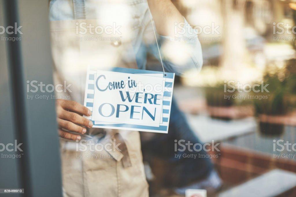 Hombre poner abierto muestra en puerta café - foto de stock