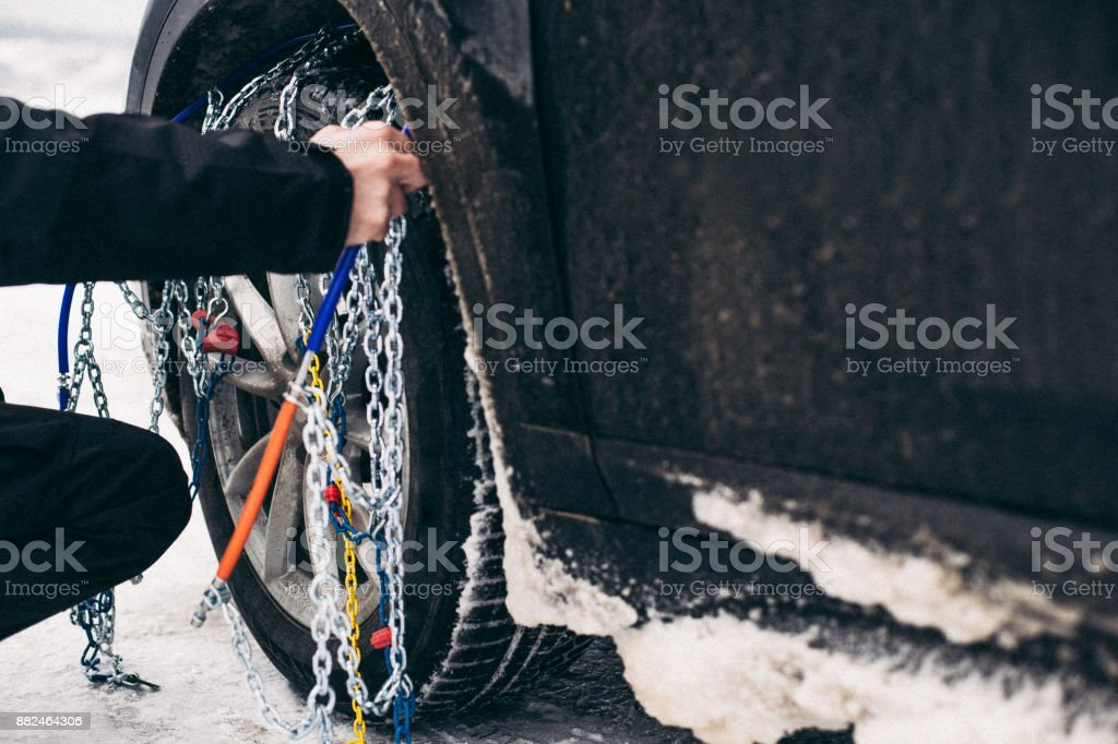 Man placing tire chains on the tire stock photo