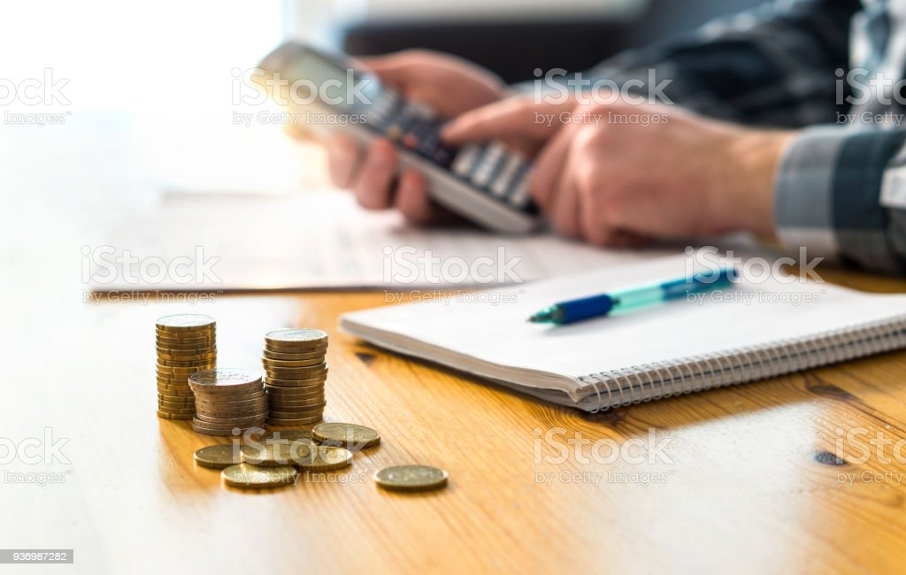Man planning family finance and using calculator. Counting savings, budget, taxes, expenses and living cost. Calculating money. royalty-free stock photo