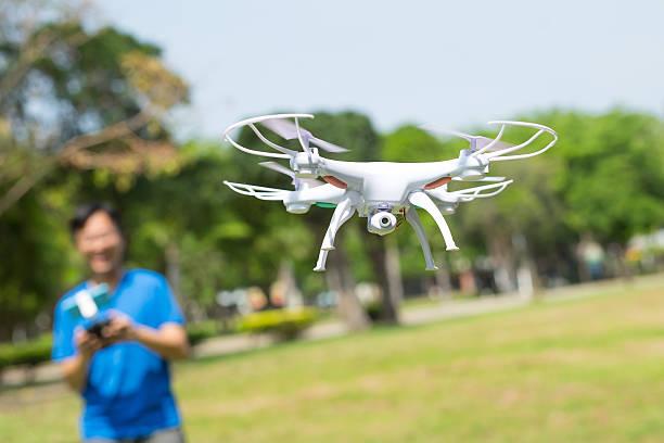 man play drone in park - flugdrohne stock-fotos und bilder