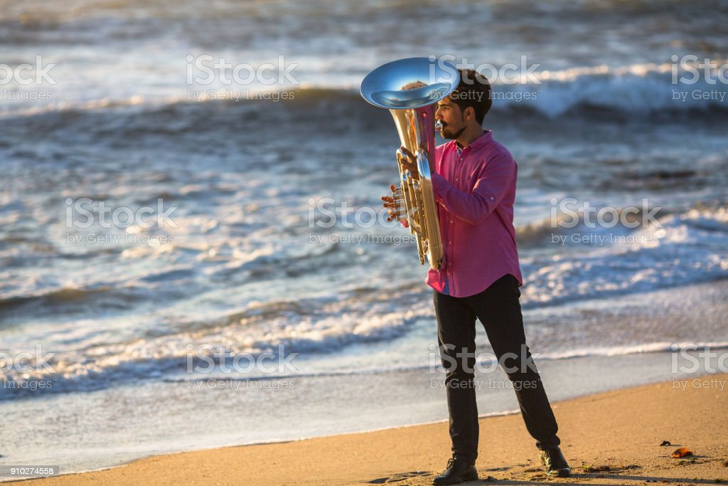 Man play the trumpet on Ocean coast during surf. stock photo