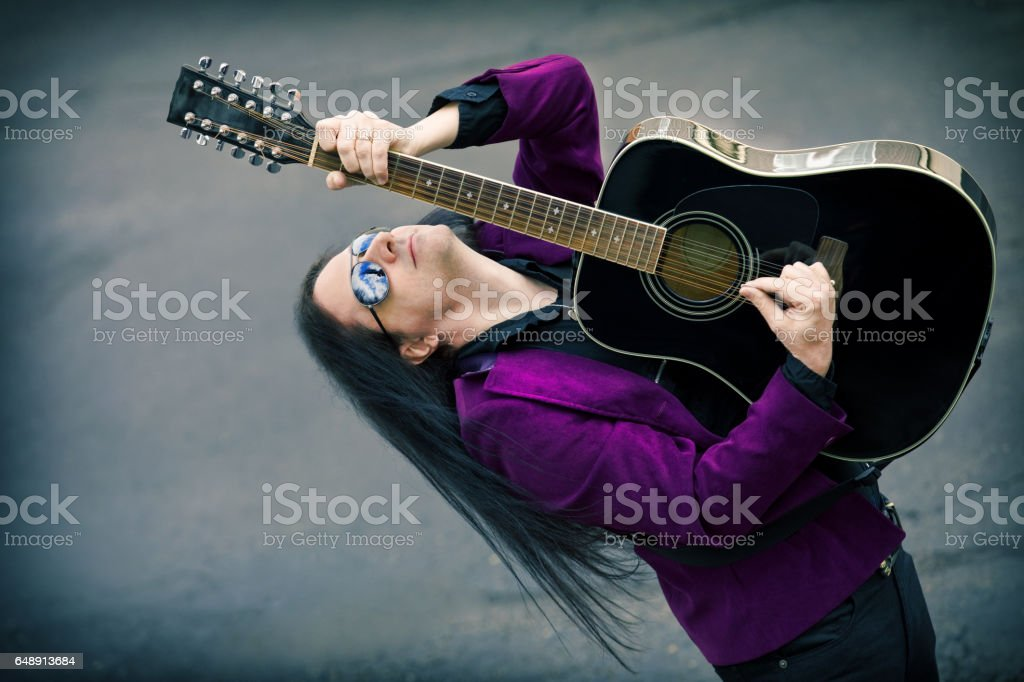 Man Playing 12 String Acoustic Guitar An attractive man with long dark hair playing a 12 string acoustic guitar. Adult Stock Photo