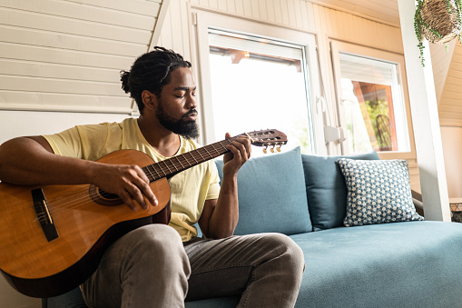 African American man playing a guitar at home.