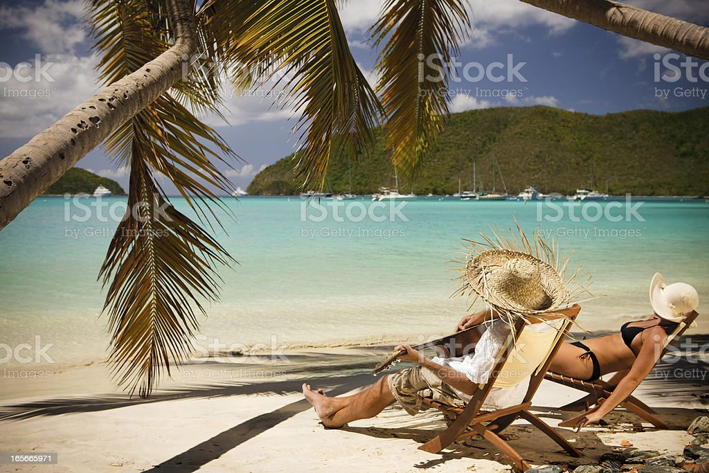 man playing a guitar at the beach, woman sunbathing stock photo