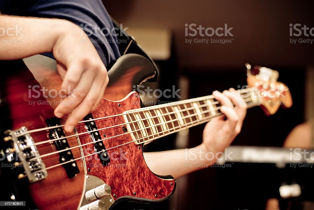 A man playing a guitar in a room stock photo